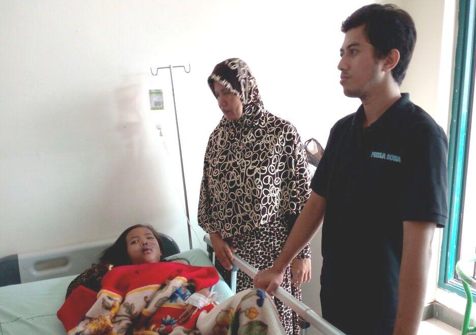 Lidya Anandasari (9) tergolek di RSUD Bangil Kabupaten Pasuruan dengan dibarengi bibi saat dijenguk pengurus dari LPA Kabupaten Pasuruan. (foto : abd)