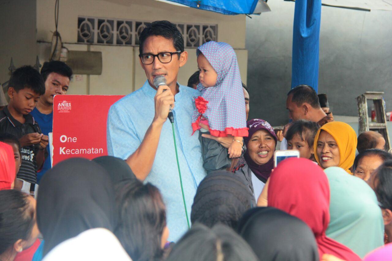 Sandiaga menggendong anak kecil.  Sandi juga berjanji kepada anak Titik yang masih balita bernama Maharatu supaya mendapatkan pendidikan yang baik di Jakarta