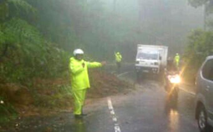 Polisi memandu kendaraan yang lewat, setelah hujan deras yang henti mengguyur kawasan Puncak,  Kabupaten Bogor meruntuhkan ikatan tanahnya sehingga tebing setinggi sekitar 15 meter yang berada di Desa Tugu Selatan, Kecamatan Cisarua, Kabupaten Bogor, mengalami longsor, Rabu (15/2/2017) sore