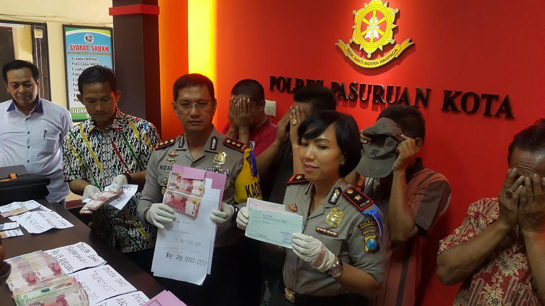 Kapolres Pasuruan Kota, AKBP Rizal Martomo dan Ketua Tim Saber Pungli Kota Pasuruan, Kompol Herlina, menunjukkan barang bukti uang Rp 93,3 juta dan berkas-berkas prona serta empat tersangka yang tertangkap dalam OTT. (abd)