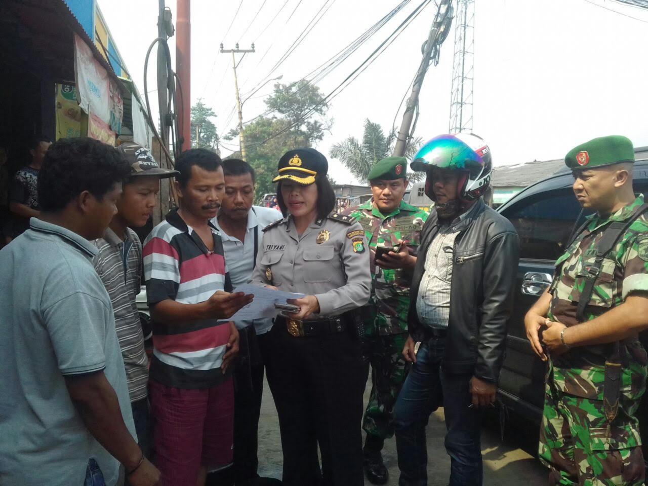 Anggota Polwan didampnigi anggota TNI membagi bagikan brosur ajakan damai, pasca bentrok antara sopir angkot dengan angkutan online.