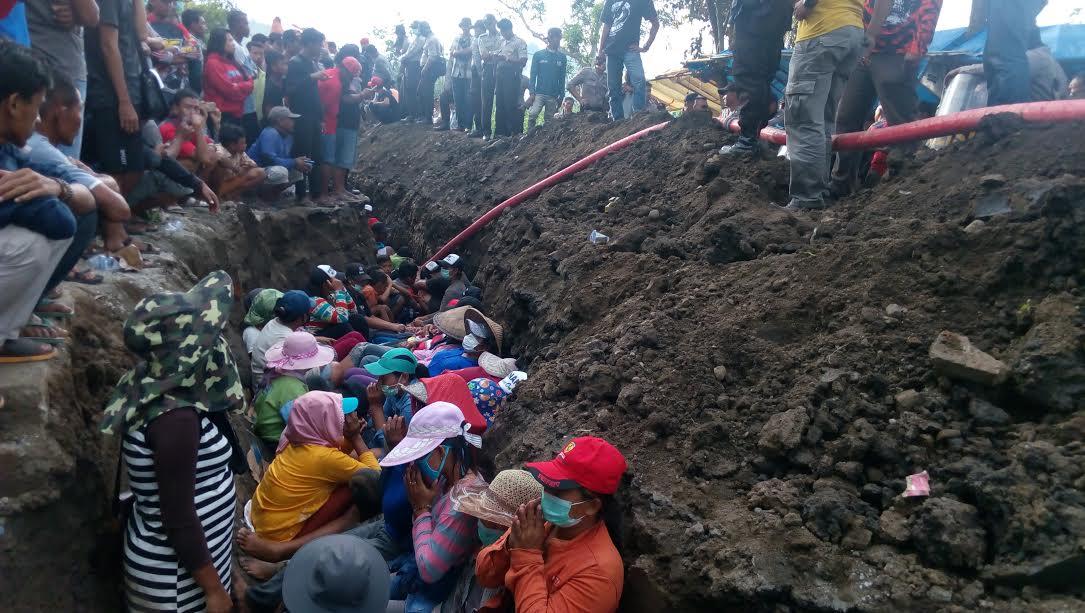 Puluhan ibu ibu nekat dukuki galian kabel dalam aksi protes keberadaan saluran listrik di wilayah mereka.