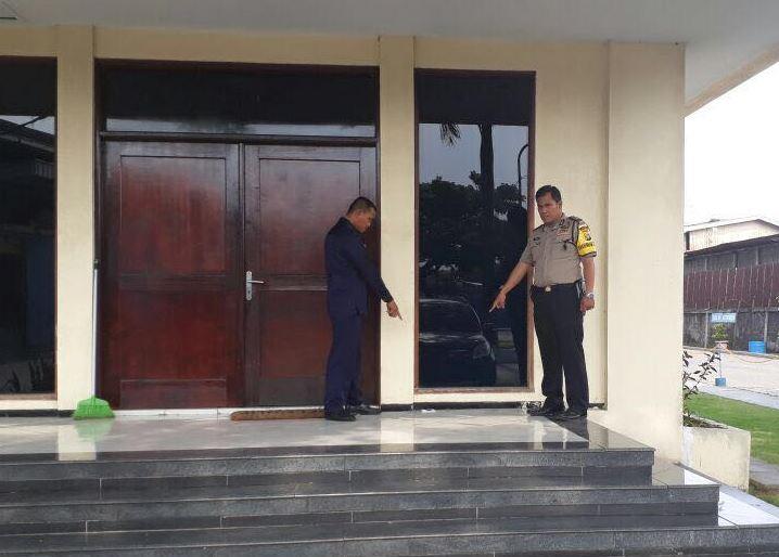 Aparat kepolisan menunjukan tempat ditemukannya surat ancaman dari orang yang mengaku anggota isis di depan pintu masuk PT RMIP