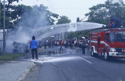 Petugas pemadam kebakaran sedang memadamkan Mobil Ketua Komisi I DPRD Lombok Tengah. (foto: zak)