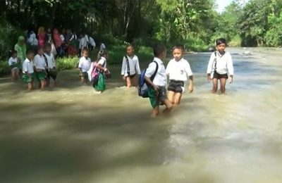 Para siswa menyeberang Sungai Rondoningo, di Dusun Kedung Mirih, Desa Opo-opo, Kecamatan Krejengan, Kabupaten Probolinggo jika hendak berangkat dan pulang sekolah.(foto: dic)