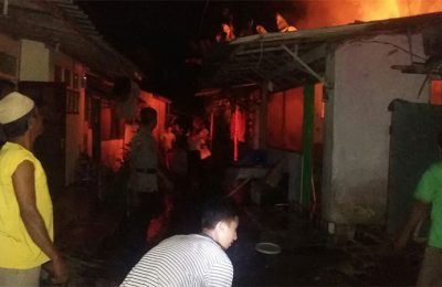 Warga berusaha memadamkan api yang membakar dua rumah warga Situbondo. (foto: fat)