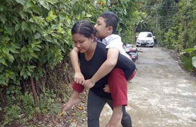 Yuliati menggendong anaknya Dio Eka Saputra yang menderita lumpuh layu. (foto: antara jatim)