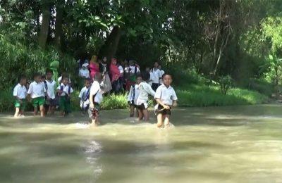 Siswa sekolah dari Yayasan Nurul Islam, di Desa Opo-opo. Kecamatan Krejengan, Kabupaten Probolinggo Jawa Timur, menyeberang sungai tanpa jembatan, dan merejkak harus bertaruh nyawa menenantang maut.(foto: dic)