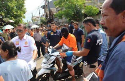 Pelaku pembunuhan  saat melakukan reka adegan dengan pengawalan polisi di Jalan Mawar, Kedaung, Pamulang, Tangerang Selatan, Rabu (31/5).