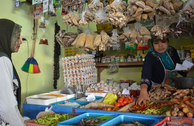 Salah satu pedagang sembako di Pasar Panji situbondo sedang melayani pembeli. (foto: fat)