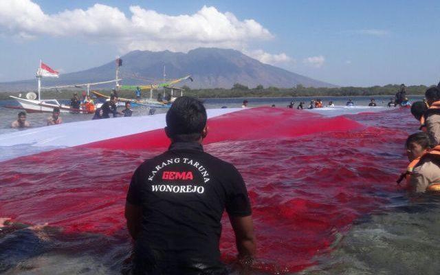 Puluhan pemuda karang taruna kebangsaan dan sejumlah elemen masyarakat Desa Wonorejo, Kecamatan Banyuputih, Situbondo, Jawa Timur, mengibarkan bendera berukuran raksasa diatas lau (foto:fat)