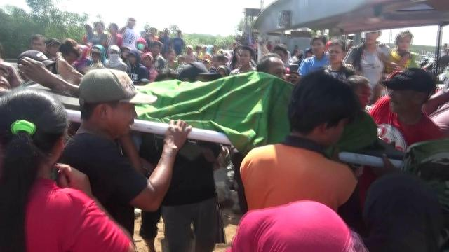 Warga dan pihak terkait saat melakukan evakuasi jasad Misnadi (korban tewas tenggelam) dari pantai utara di Desa Pesisir, Kecamatan Gending, Kabupaten Probolinggo Jawa Timur.(foto: dic)