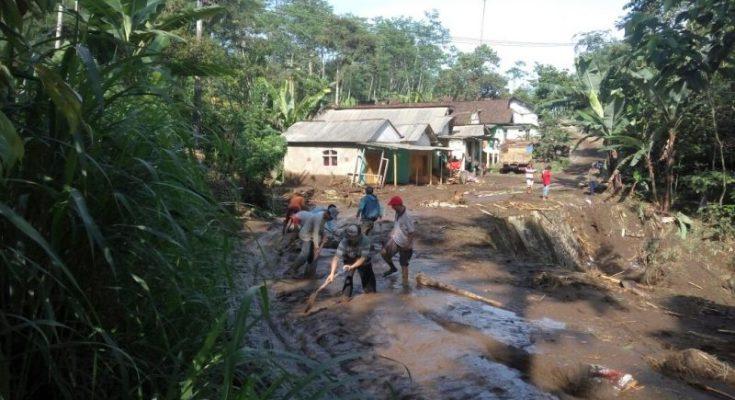 Warga bergotong royong membersihkan lumpur di jalan utama yang lumpuh total.(foto: dic)