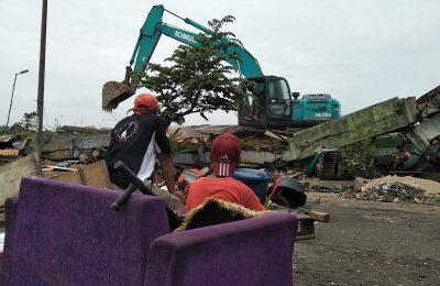 : Warga menyaksikan alat berat membongkar bangunan eks Terminal Kota Tasikmalaya yang menjadi tempat tinggalnya. (foto:ap)