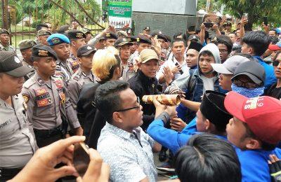 Puluhan mahasiswa PMII terlibat aksi saling dorong dengan petugas di depan kantor Pemkab SItubondo. Mereka  meminta agar Sekda segera dicopot. (foto:fat)