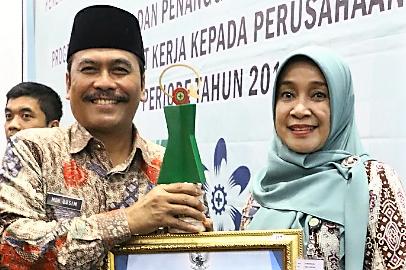 Wabup HM Qosim bersama Kadisnaker Pemkab Gresik Ninik Asrukin saat menerima Penghargaan Pembina Terbaik K3. (Foto:dik)