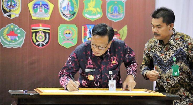 Bupati Gresik Sambari Halim Radianto saat menandatangani komitmen pemberantasan korupsi bersama KPK. (foto:dik)