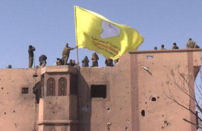 Pasukan Demokratik Suriah mengibarkan bendera kuning di atas bangunan yang disita dari ISIS di Baghuz.