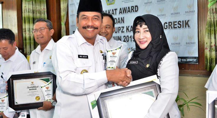 Penasehat Baznas Kabupaten Gresik H Moh Qosim saat memberikan apresiasi kepada salah satu unit pengumpul zakat. (foto: dik)
