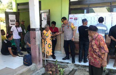 Kapolres Rote Ndao AKBP Bambang Hari Wibowo membantu seorang wanita lansia yang menggunakan hak pilihnya pada Pilpres dan Pileg 2019, Rabu (17/4/2019). (Ist)