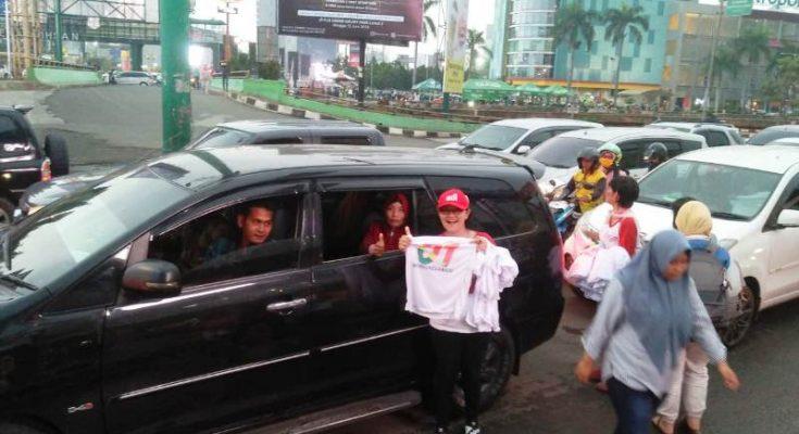 Anggota belUSUkan membagikan kaos paslon 01 kepada para pengendara di perempatan Jalan Jenderal Ahmad Yani dan Jalan KH Noer Ali, Kota Bekasi, Minggu (7/4/2019). (Ist)