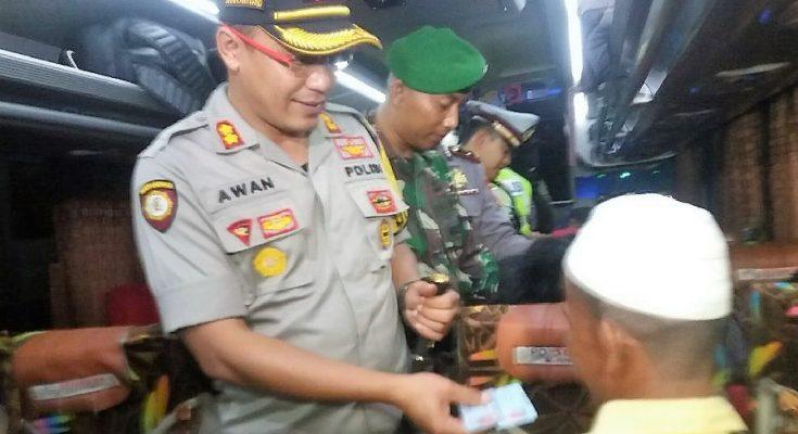 Kapolres AKBP Awan Hariono, saat memeriksa identitas atau KTP para penumpang bis. (foto:fat)