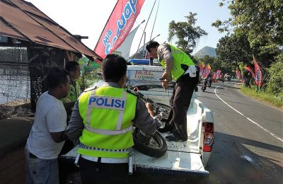 polisi tengah mengangkut kendaraan bermotor yang ringsek setelah ditabrak truk. (foto:fat)