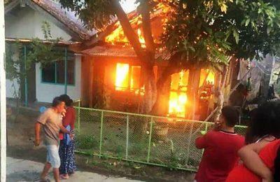 Sejumlah warga tengah berusaha memadamkan kobaran api yang membakar rumah seorang warga di Situbondo. (foto:fat)