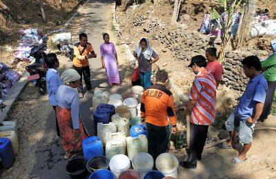 Sejumlah warga tengah mengantri air bersih yang disdtribusikan BPBD Situbondo. (foto:fat)