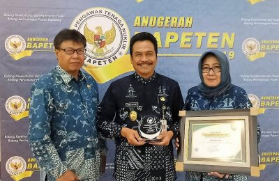 Wabup Qosim didampingi Plt. Kadinkes Gresik dr. Endang Puspitowati dan Kepala DLH Ir. Mokh. Najikh saat menerima penghargaan. (foto:dik)