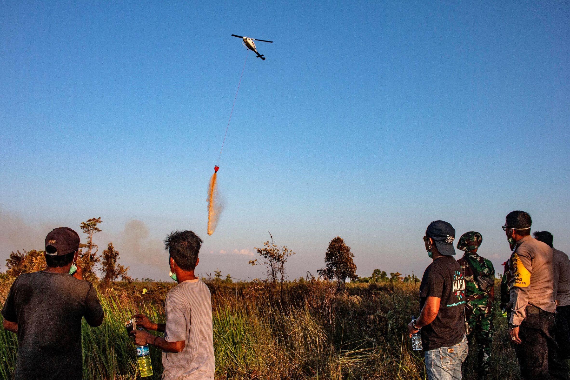 Sebuah helikpter diterjunkan untuk memadamkan kobaran api yang membakar lahan lahan gambut. (foto:ist)