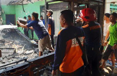 Petugas bersama warga saat membantu memedamkan api yang membakar tiga rumah warga di Situbondo. (foto:fat)