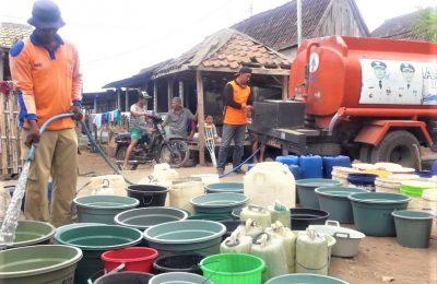 Petugas Pusdalop BPBD Situbondo, saat mendistribusikan air bersih ke salah satu dusun terdampak kekeringan. (foto:fat)