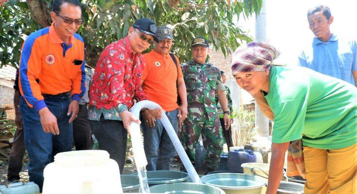 Wabup Yoyok mengisi air ke ember warga di Dusun Secangan, Desa Kalisari, Kecamatan Banyuglugur. (foto:fat)