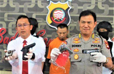 Polisi menunjukan baranag buklti senjata api milik seorang pria. (foto:das)