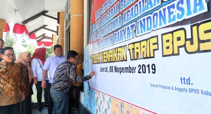 Anggota DPRD Situbondo, saat menandatangani banner penolakan kenaikan iuran BPJS. (foto:fat)