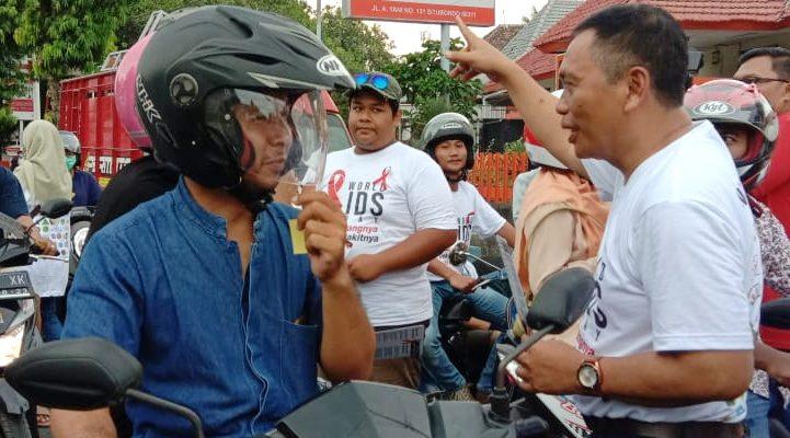 Wabup Yoyok Mulyadi, saat membagikan dan stiker kepada para pengendara kendaraan bermotor di Jalur Pantura Situbondo. (foto:fat)