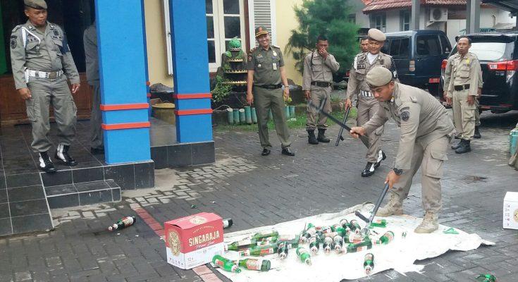 Kegiatan pemusnahan puluhan botol miras di depan kantor Satpol PP Pemkab Situbondo. (foto:fat)