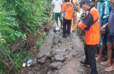 Petugas Pusdalop BPBD Situbondo, saat meninjau lokasi jalan desa yang retak. (foto:fat)