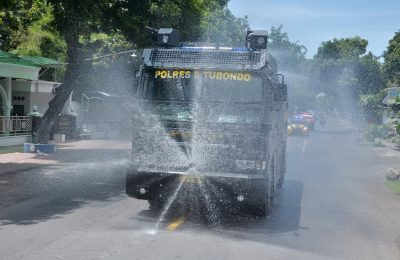 Kendaraan water canon milik polres Situbondo saat menyemprotkan cairan disinfektan di kota Situbondo. (foto:fat)