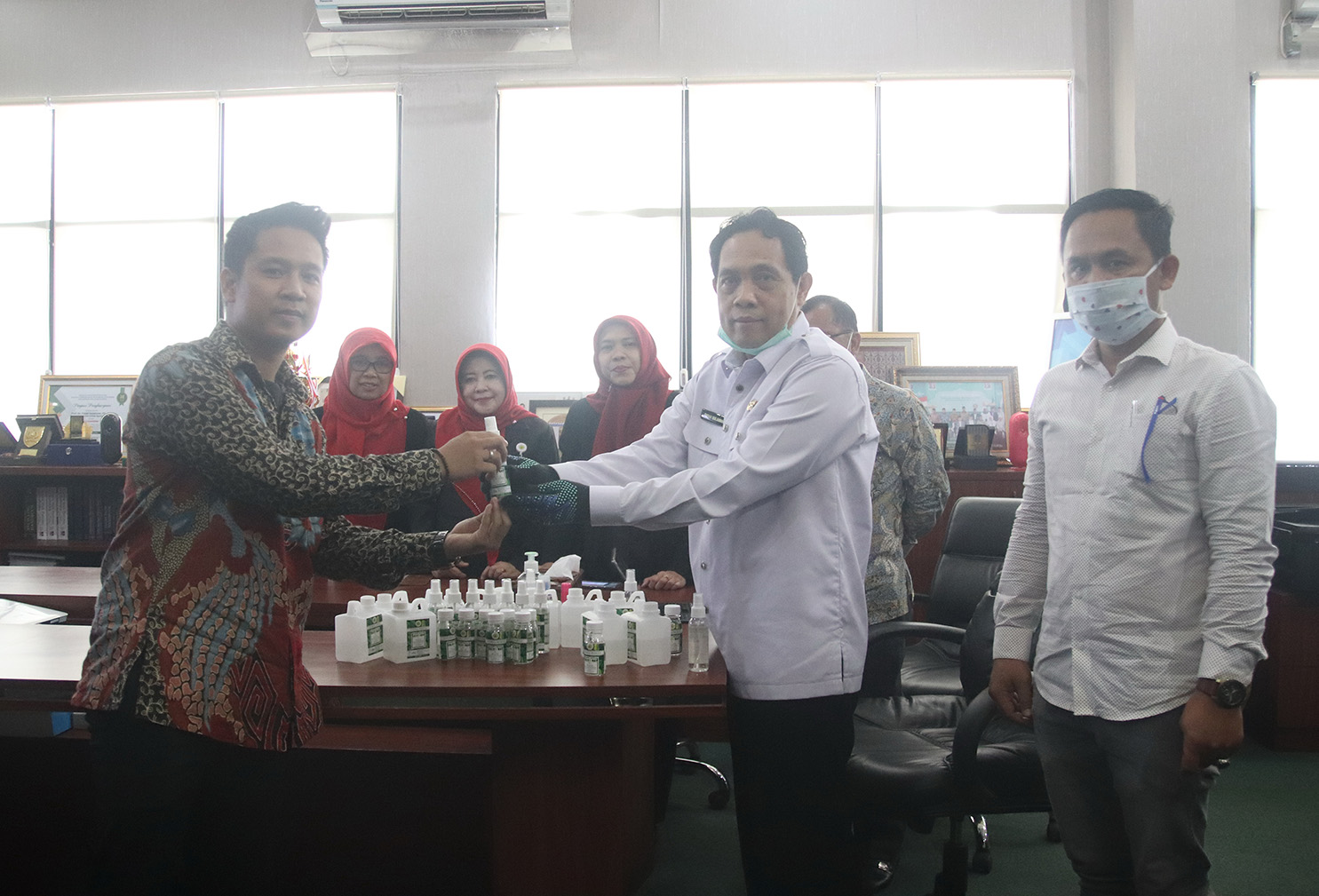 Penyerahan secara simbolis hand sanitiser kepada perwakilan mahasiswa untuk didistribusikan kepada warga. (foto:ist)