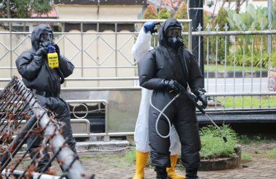 dengan menggunakan alat pelindung diri (APD) lengkap, tim Unit Brimob melakukan penyemprotan cairan disfektan. (foto:das)