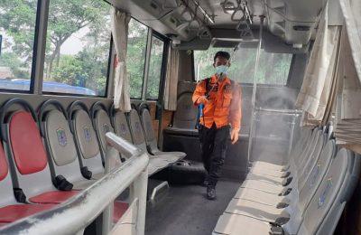 Petugas BPBD Binjai melakukan penyemprotan disinfektan di dalam Bis. (foto:van)
