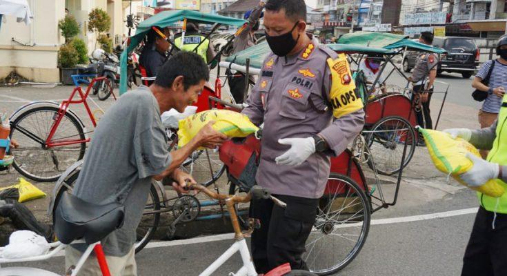 Kapolresta Pontianak Kota Kombes Pol Komarudin saat membagikan bantuan beras kepada warga. (foto:das)