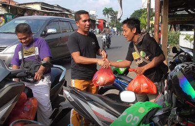 Warga Taman Mutiara Cileduk, Kota Tangerang, membagikan paket sembako kepada pengemudi ojek online di pangkalan. (foto.dik)