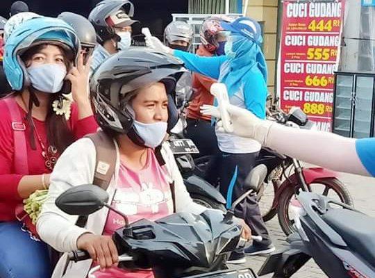 Para pengendara motor diperisa suhu tubuhnya oleh petugas.