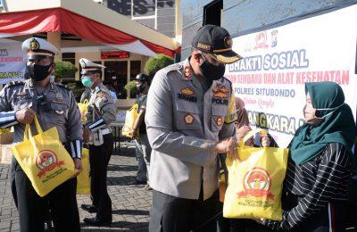 Kapolres AKBP Sugandi, saat membagikan paket sembako kepada salah seorang warga terdampak Covid-19 di Mapolres Situbondo. (foto:fat)