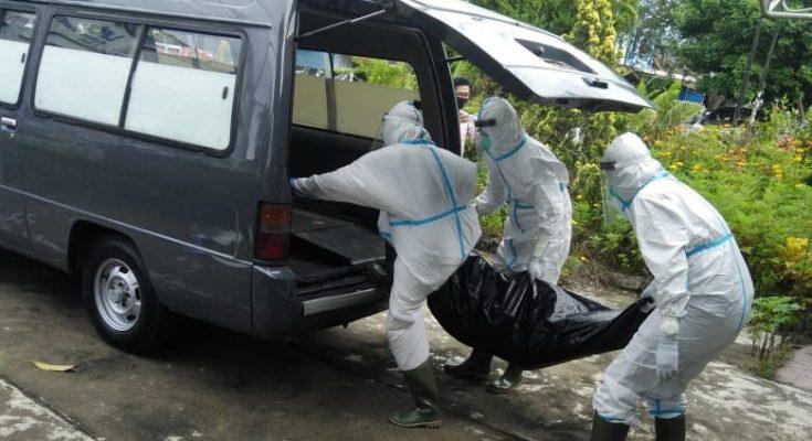 Petugas mengevakuasi jenazah seorang kakek yang tewas di rumahnya dengan menerapkan protokol kesehatan. (foto:das)