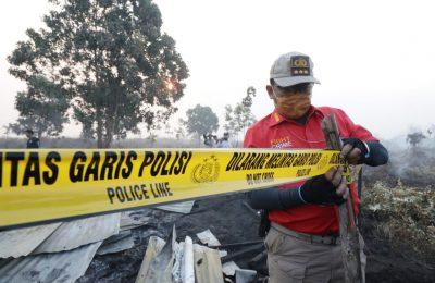 Petugas memasang garis polisi di lokasi kebakaran hutan. (foto:ist)